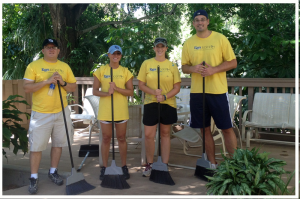 Volunteer group with brooms on West House patio
