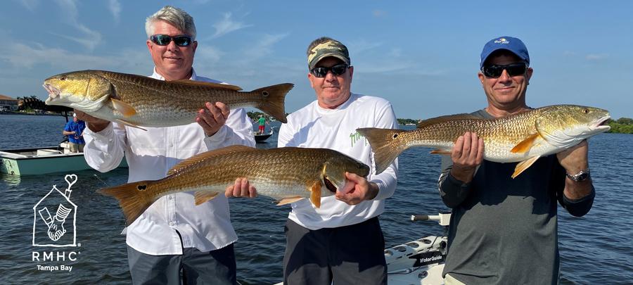 3 anglers holding giant redfish